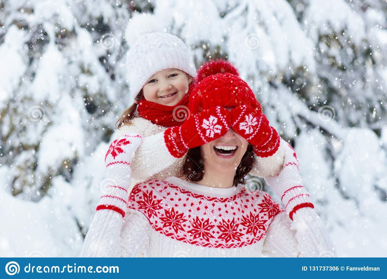 Mother and child in knitted winter hats play in snow on family Christmas vacation. Handmade wool hat and scarf for mom and kid.