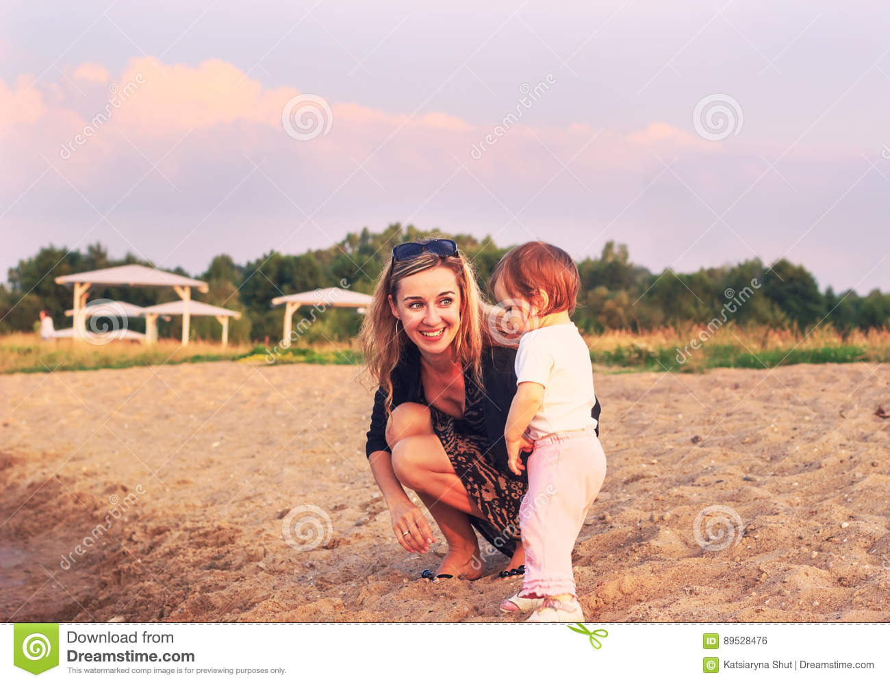 Mother and child playing on the beach at the sunset time. Concept of friendly family.