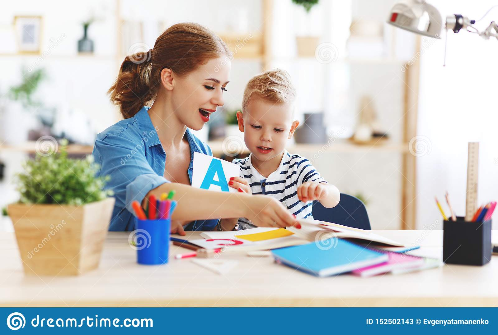 Mother and child son doing homework writing and reading at home