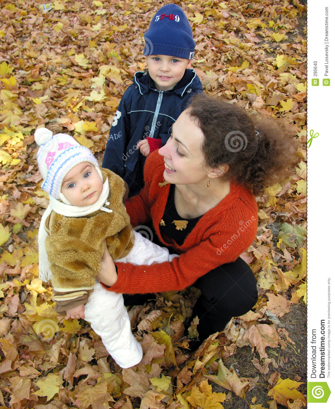 Mother with children on autumn leaves