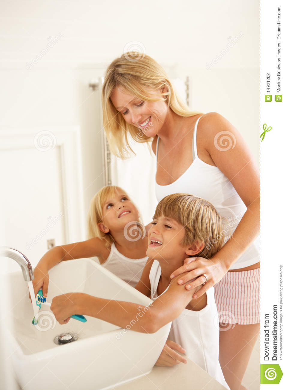 Mother And Children Brushing Teeth In Bathroom Stock