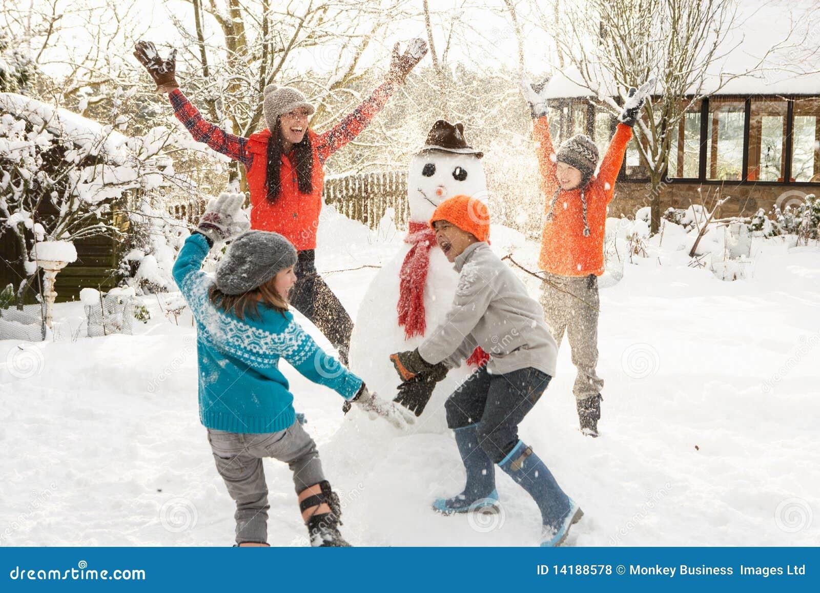 Mother And Children Building Snowman In Garden