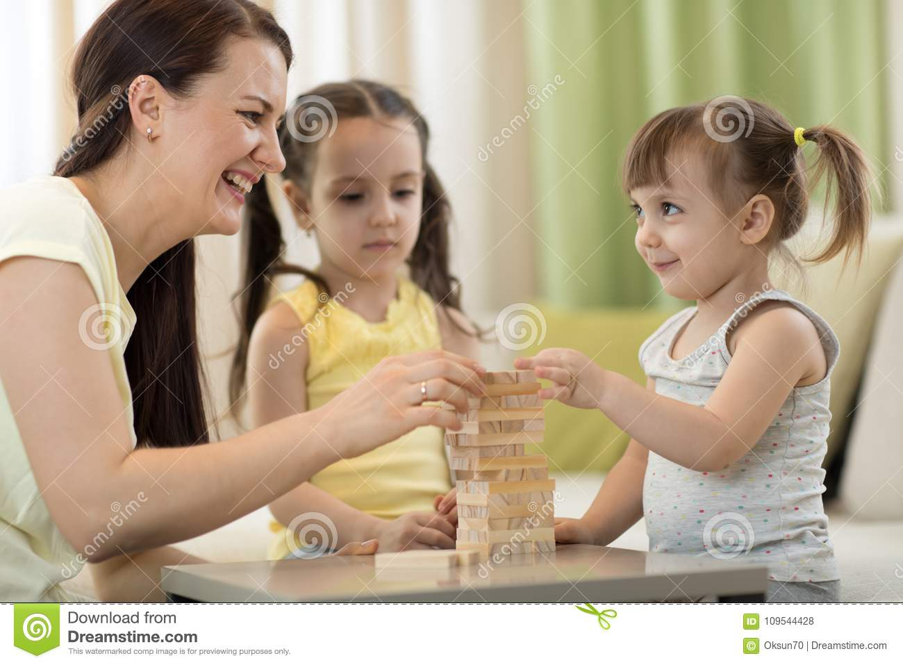 Mother and her little daughters are playing with board game