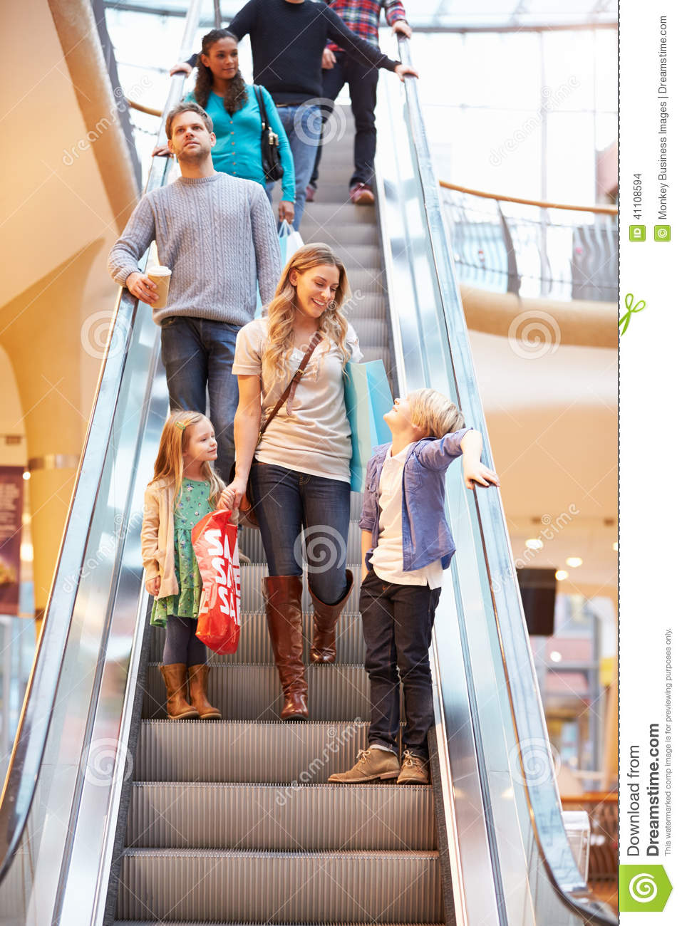Mother And Children On Escalator In Shopping Mall Stock