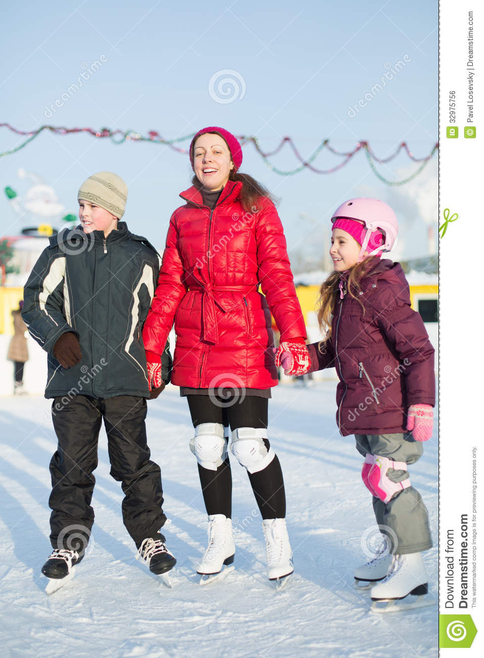 A mother with children standing on the outdoor skating rink