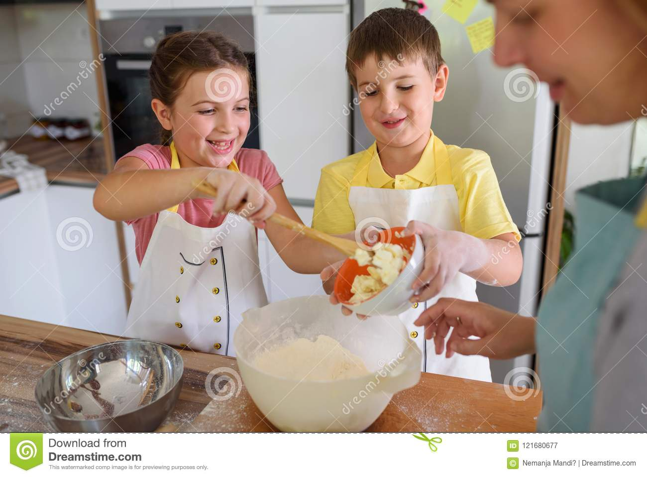 Mother And Children Together Making Apple Pie In The Kitchen At Home