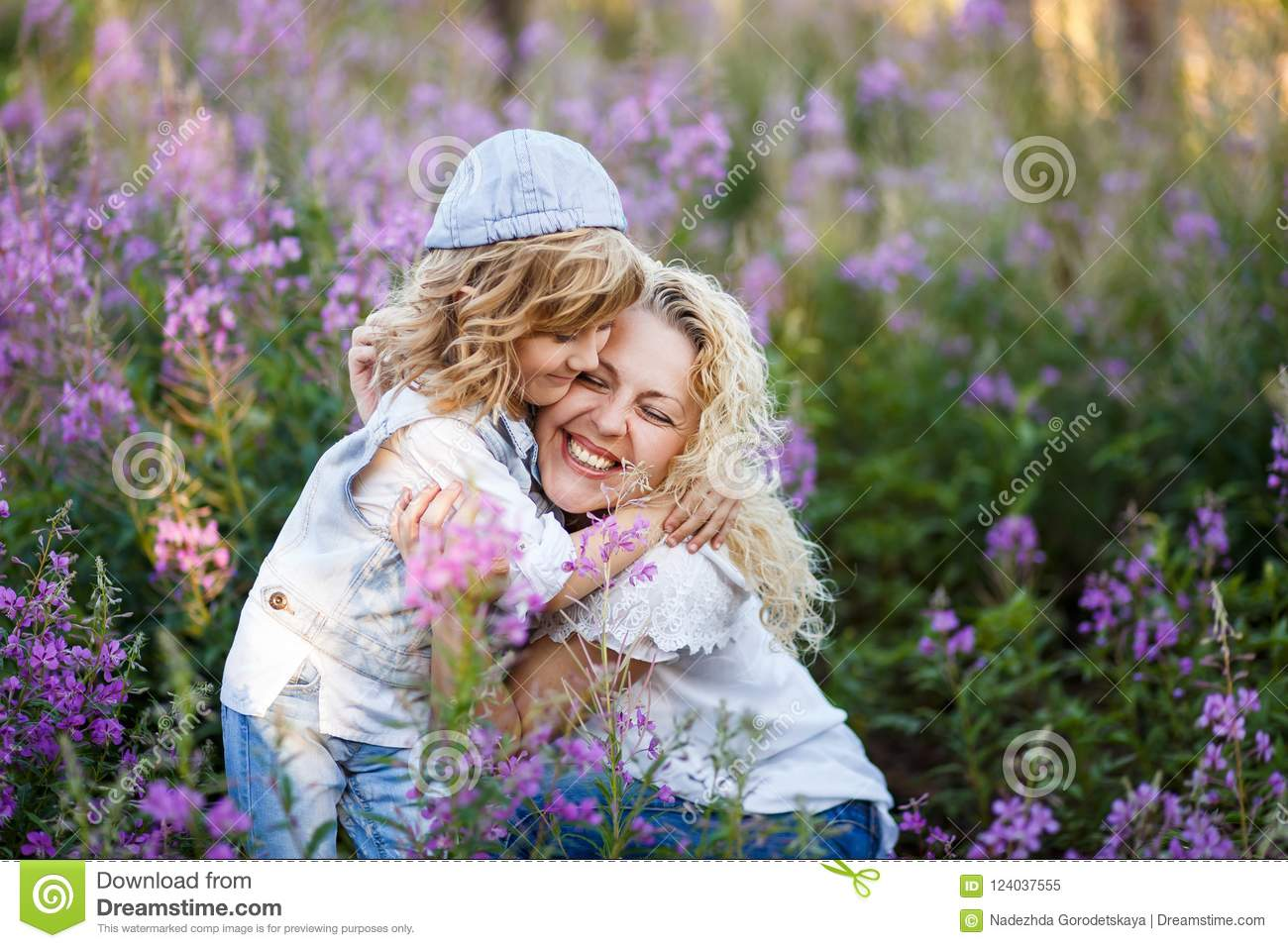 Mother and a cute little son hugging and having fun in the fild with flowers in summer. Family and happiness consept