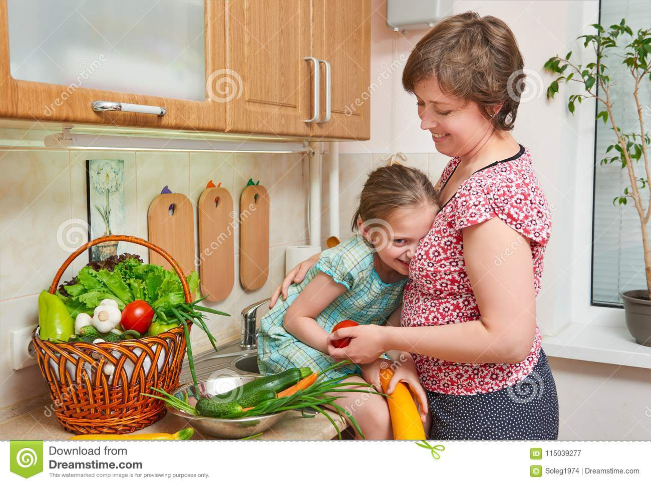 Mother And Daughter With Basket Of Vegetables And Fresh Fruits In