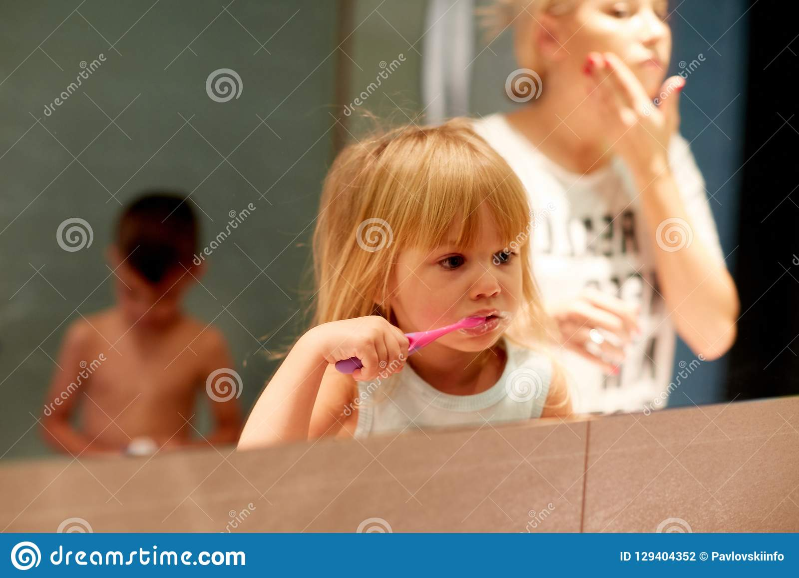 Mother And Child Brushing Teeth In Bathroom Stock Photo