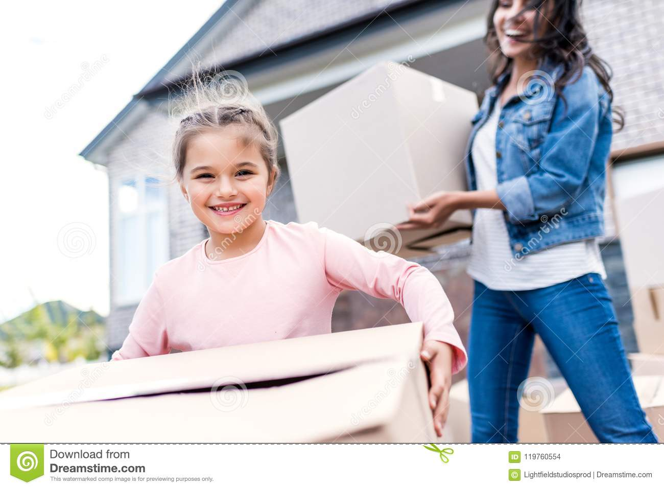 mother and daughter carrying boxes for moving into