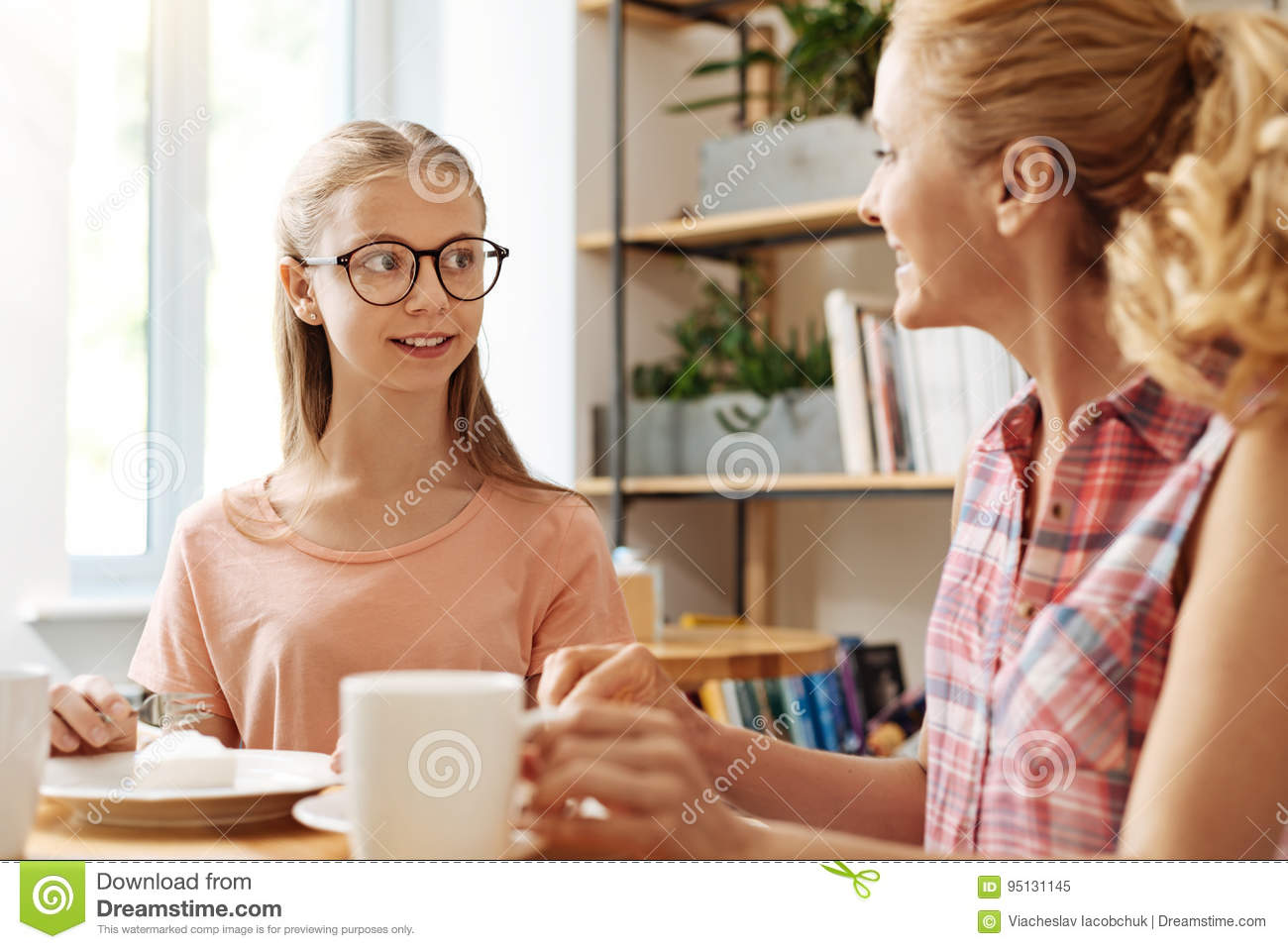 d67495db1455 Pretty teenage girl talking with her mother, discussing her school life  while relishing delicious cake and coffee. More similar stock images