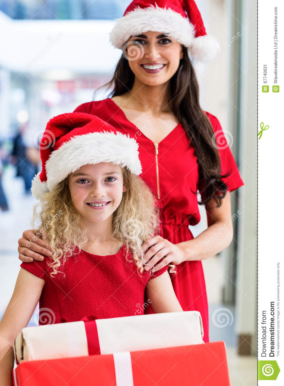 Mother And Daughter In Christmas Attire Standing With Christmas ...