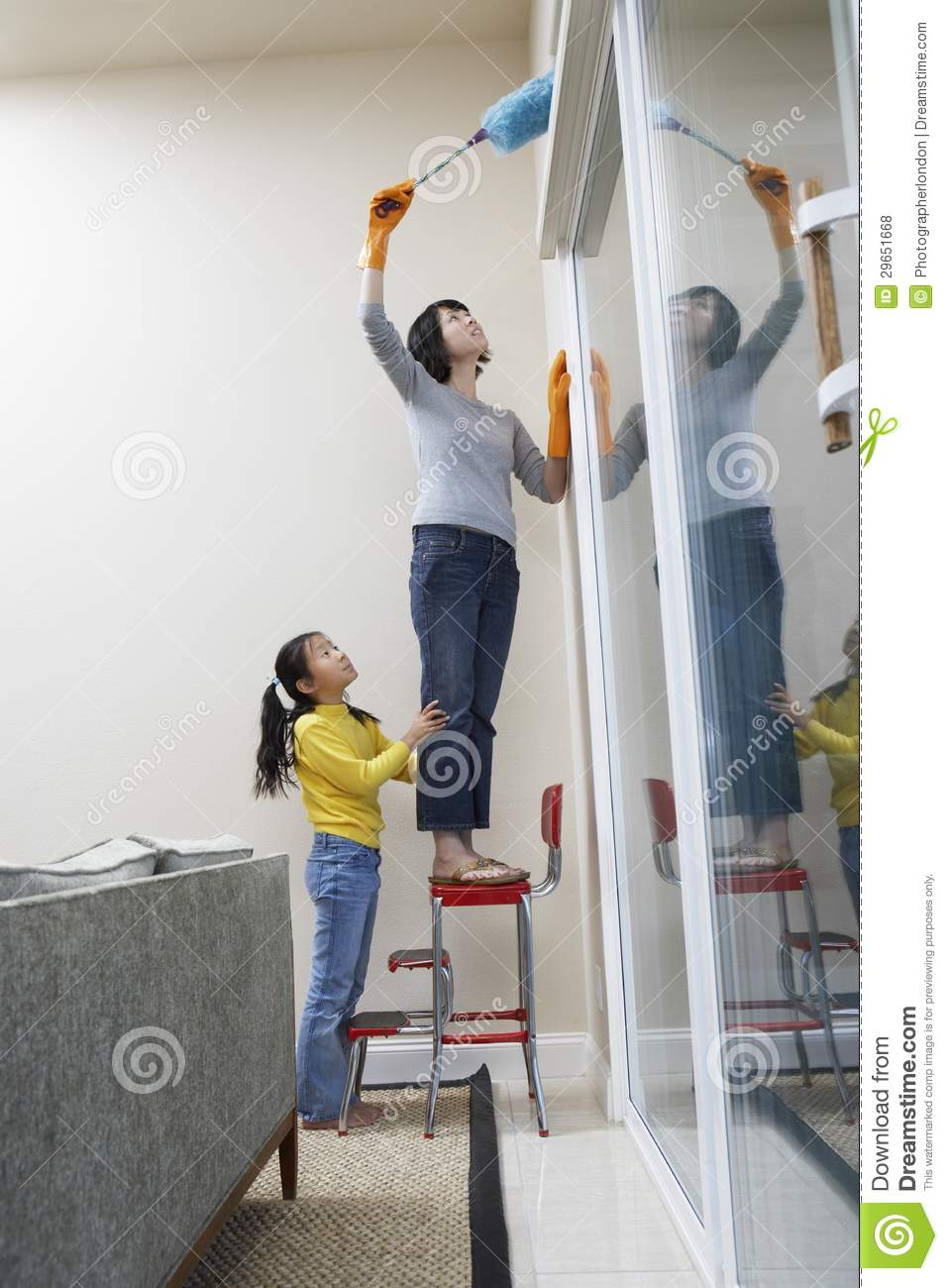 mother and daughter cleaning the house stock photo