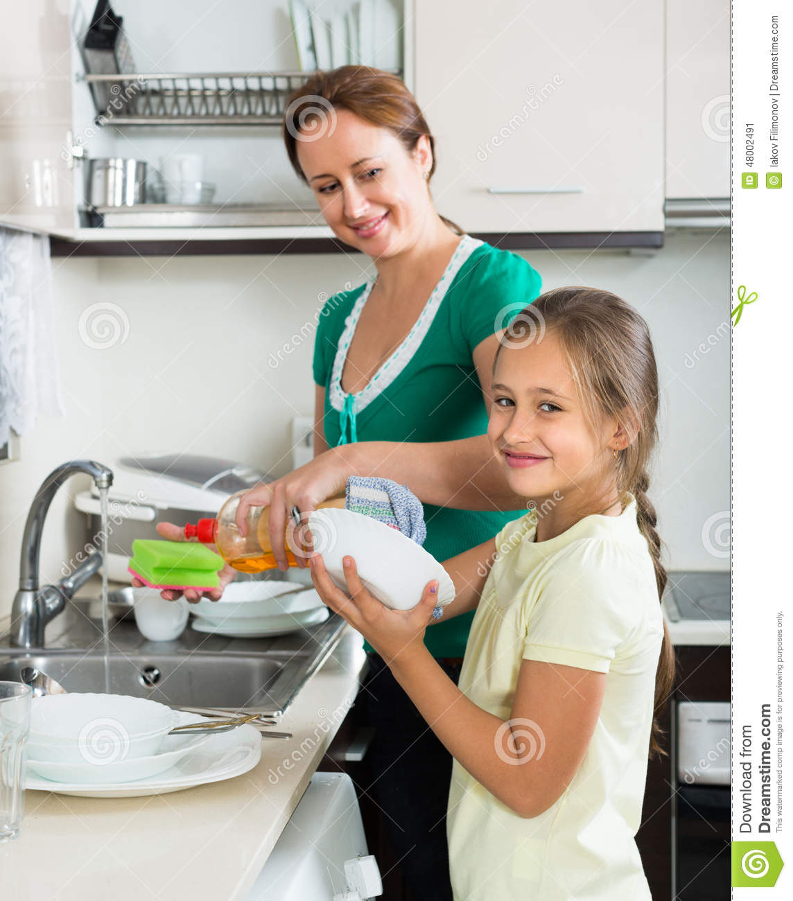 People Cleaning Kitchen: Mother With Daughter Cleaning At Kitchen Stock Image