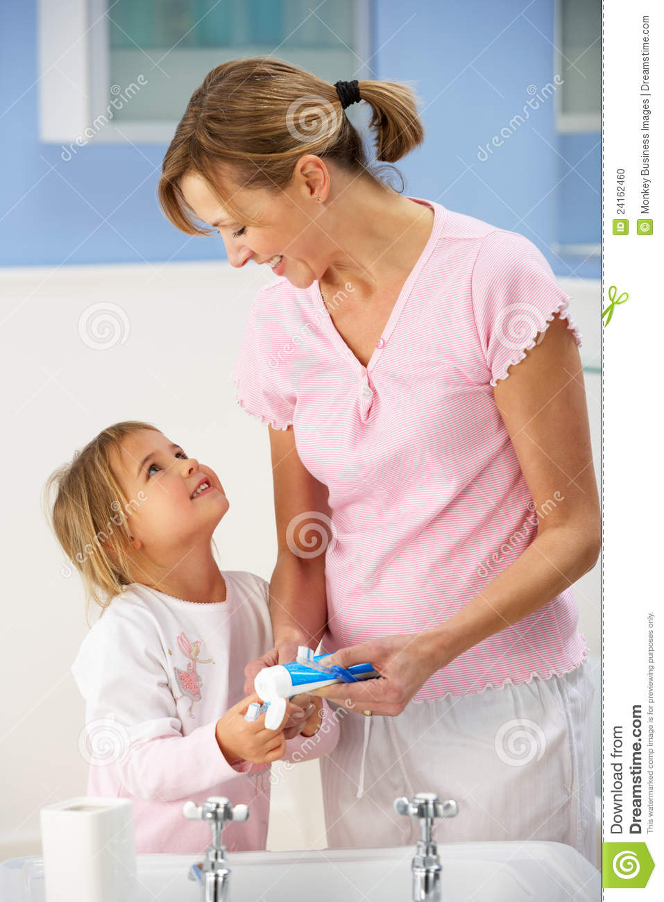 Mother And Daughter Cleaning Teeth In Bathroom Stock Photo