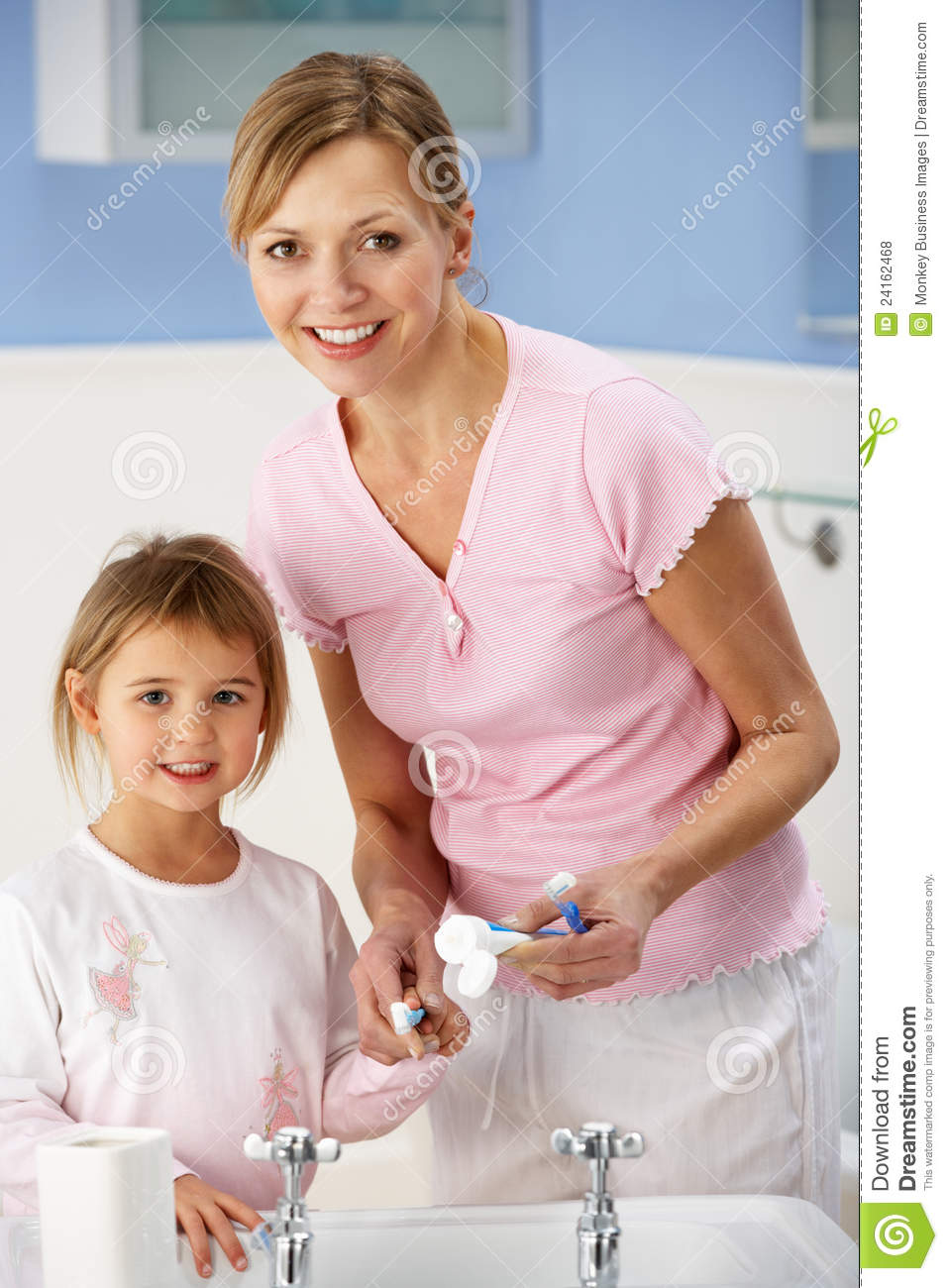 Mother And Daughter Cleaning Teeth In Bathroom Royalty