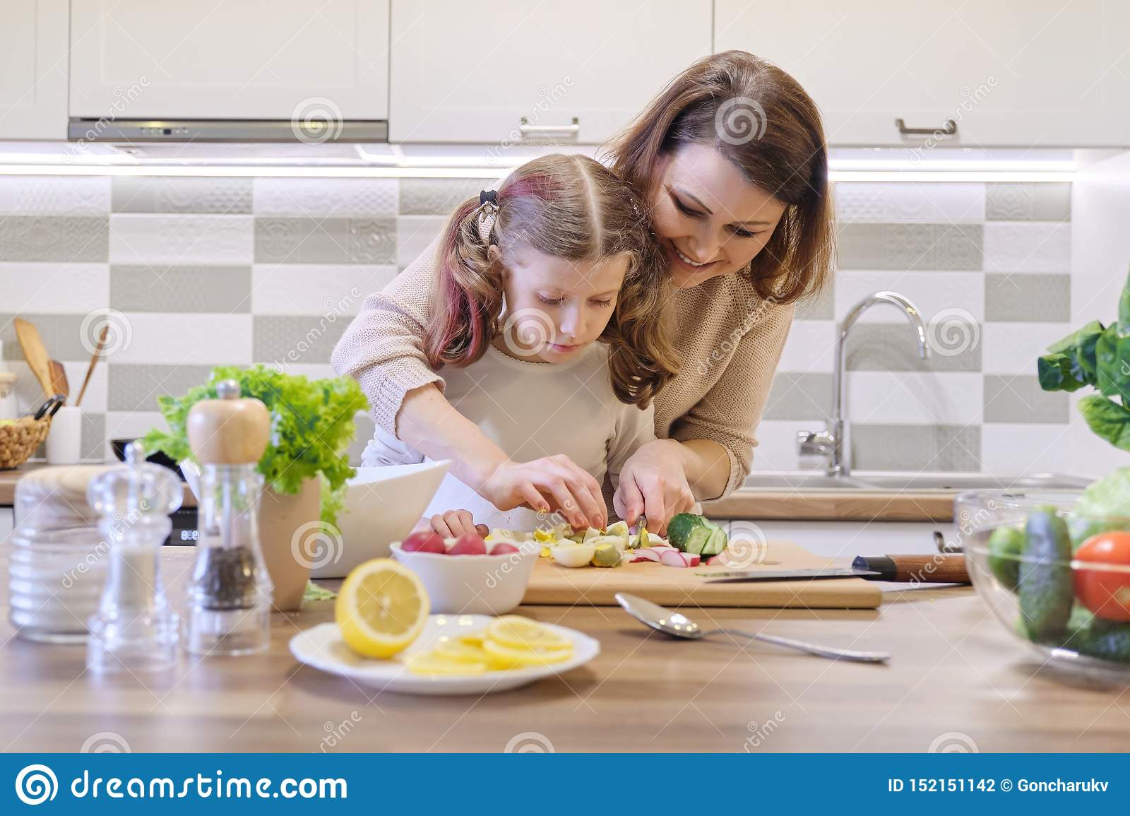 Mother and daughter cooking together in kitchen vegetable salad, parent and child are talking smiling