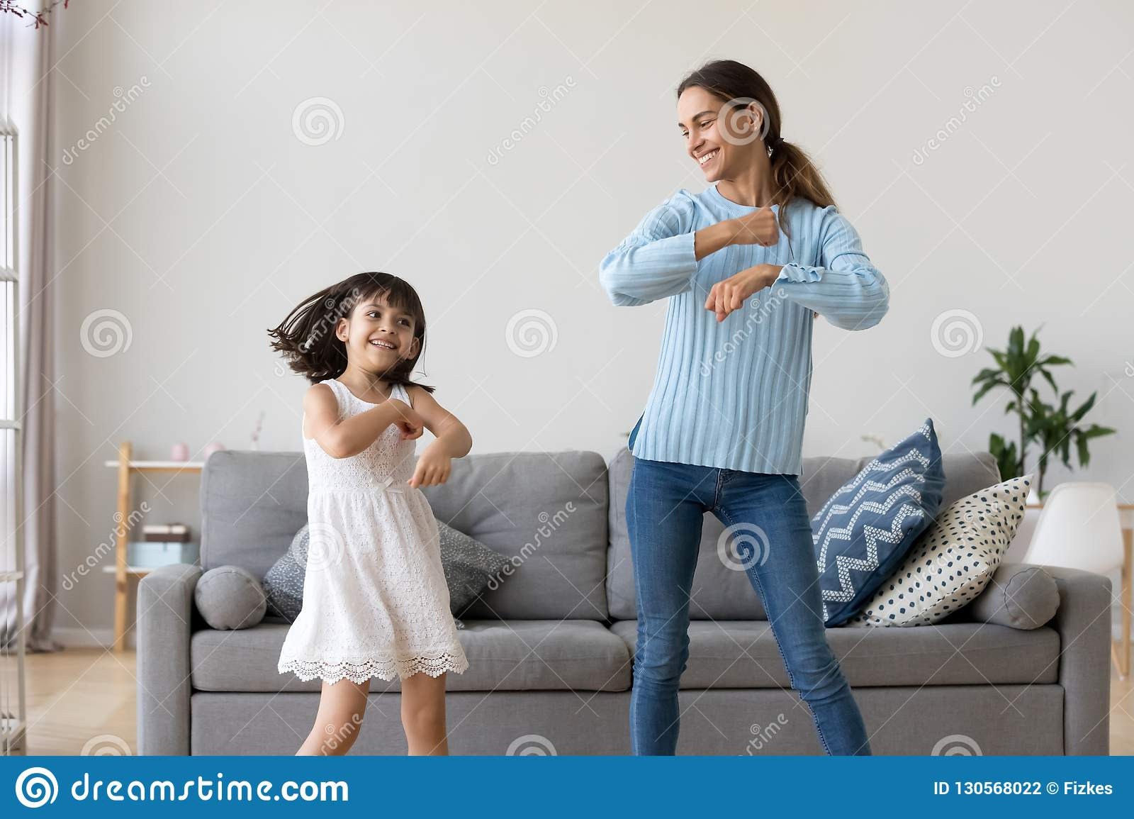 871b28f1bb Cheerful mother little daughter standing in living room at home moving  dancing to favourite song together. Child have fun with elder sister nanny  or loving ...