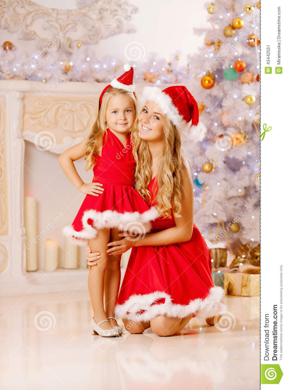 Mother And Daughter Dressed As Santa Celebrate Christmas