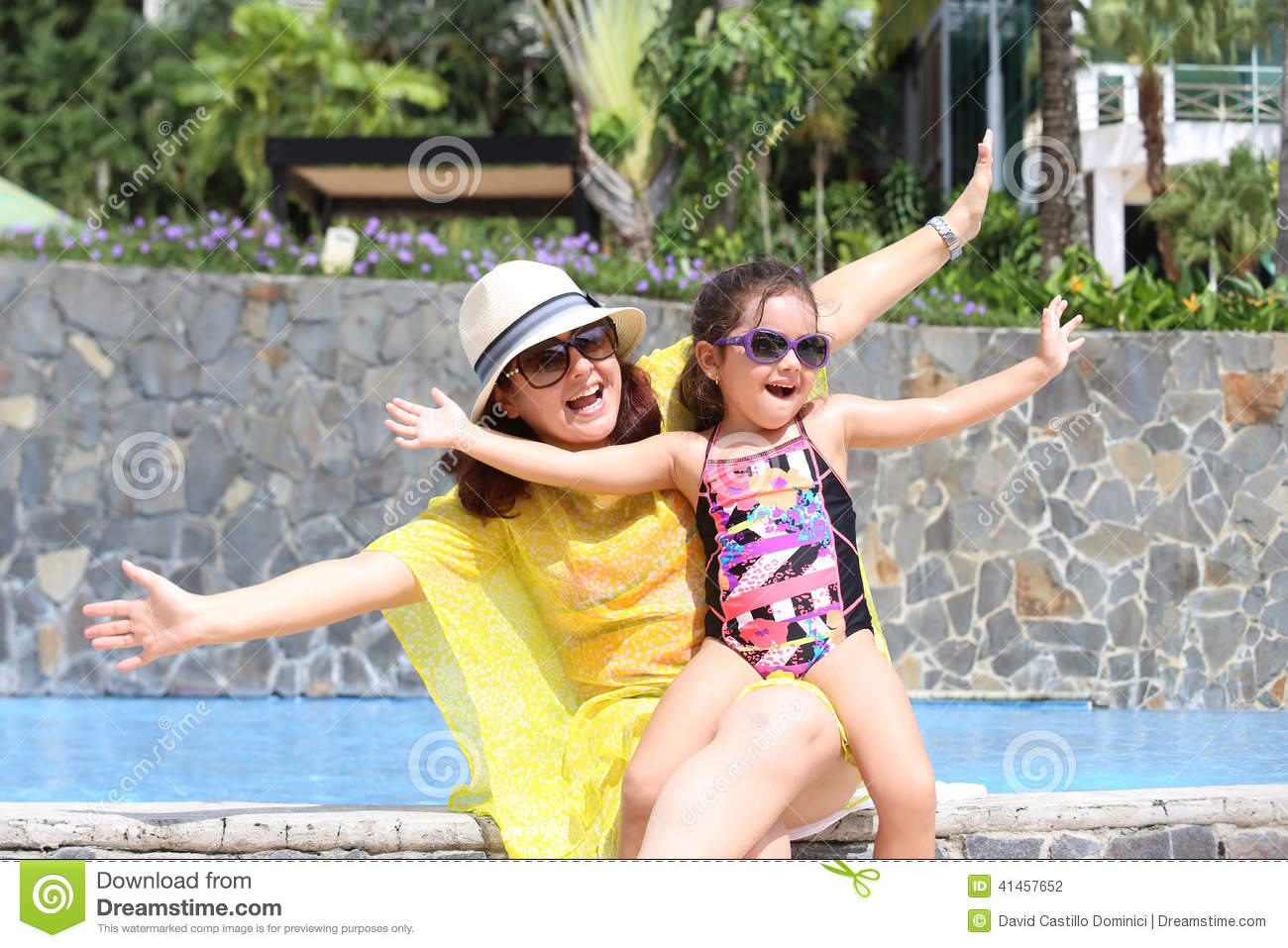 Mother and daughter happy in the pool with open arms enjoying th