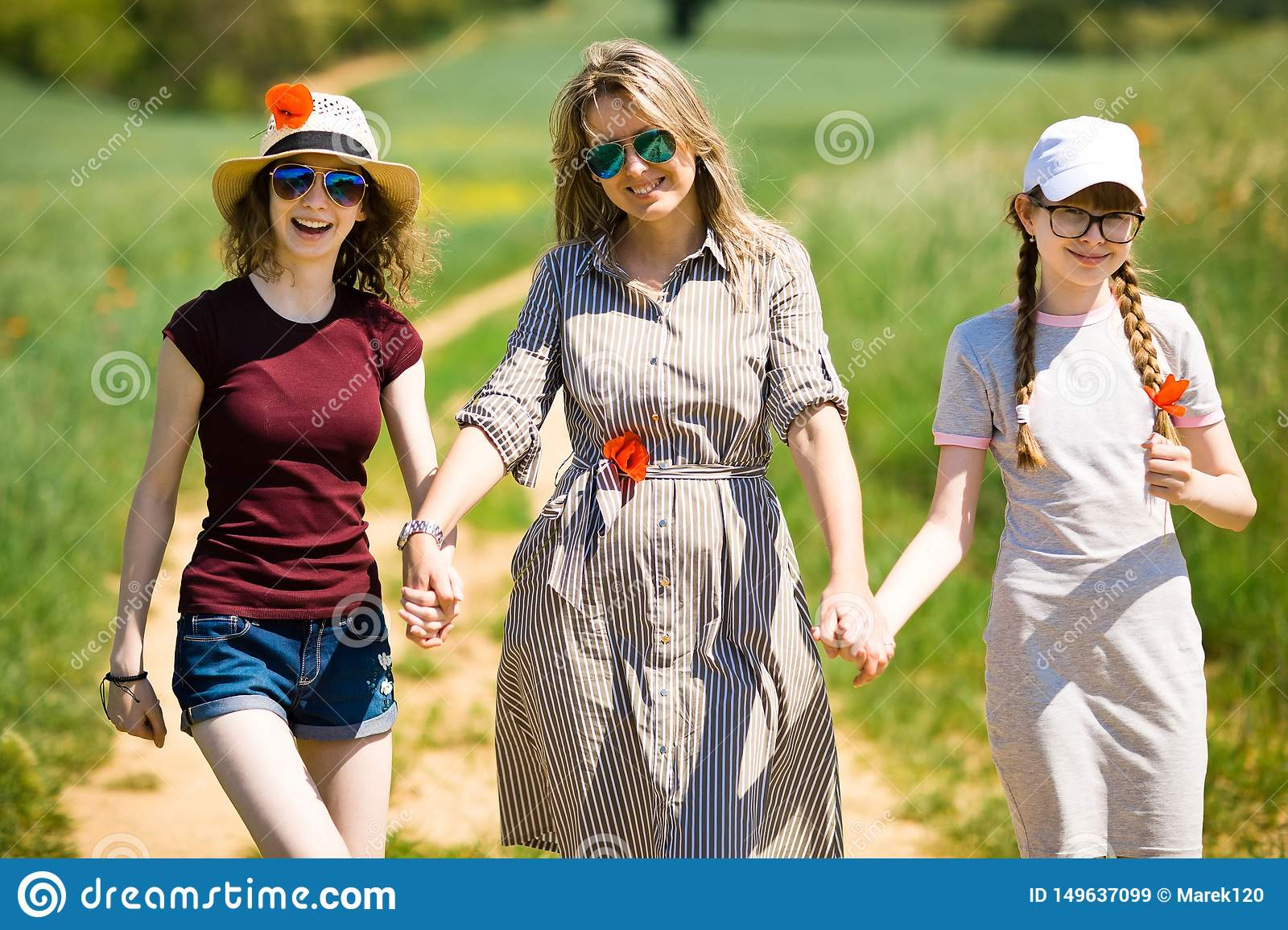 Mother with daughter having poppy flowers are walking on cart road