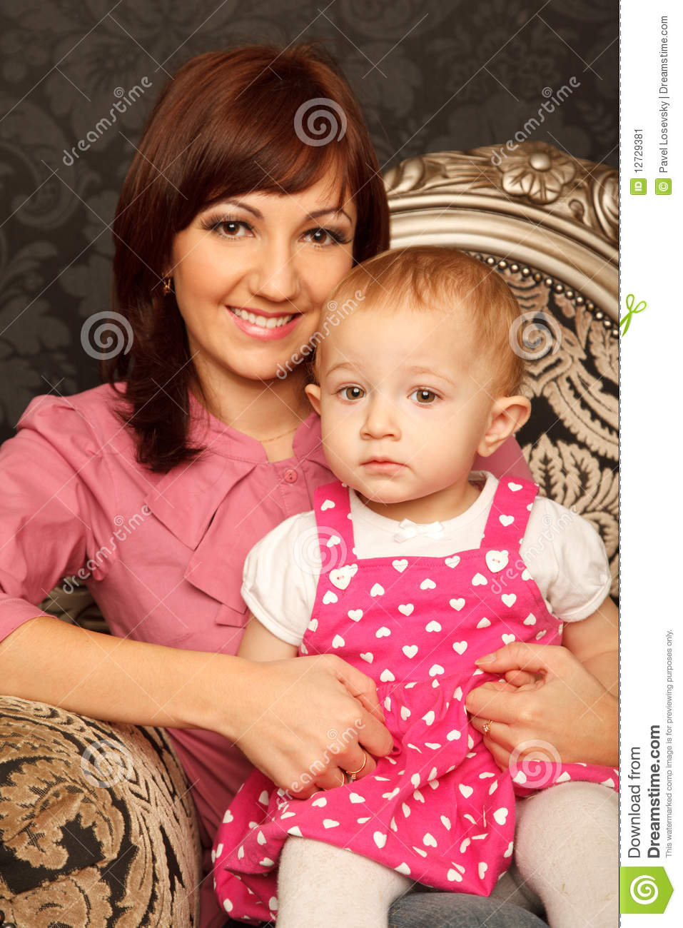 Mother and daughter on her lap sitting in armchair. Interior in retro ...