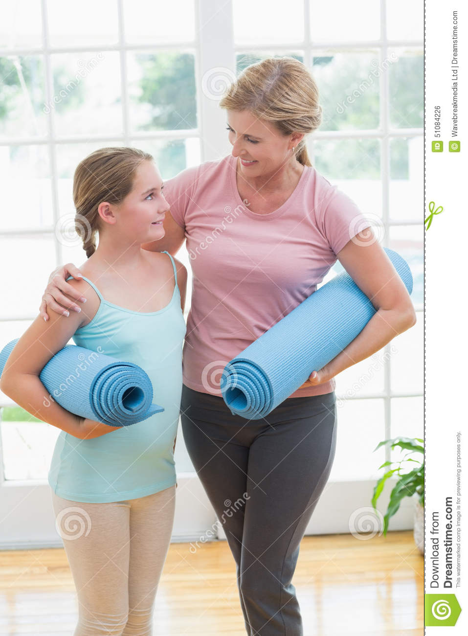 Mother and daughter holding yoga mats stock photo image for Living room yoga timetable