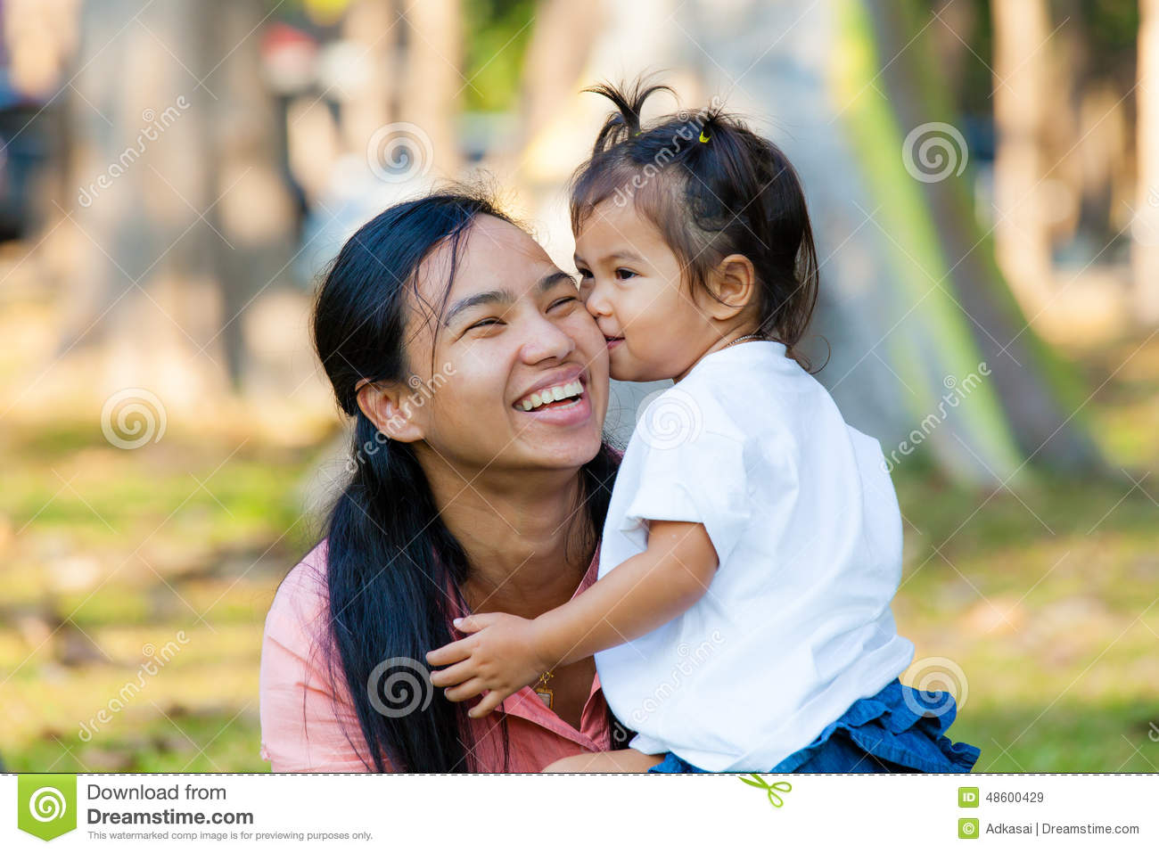 mother and daughter are hug and kiss. family is thailand. stock