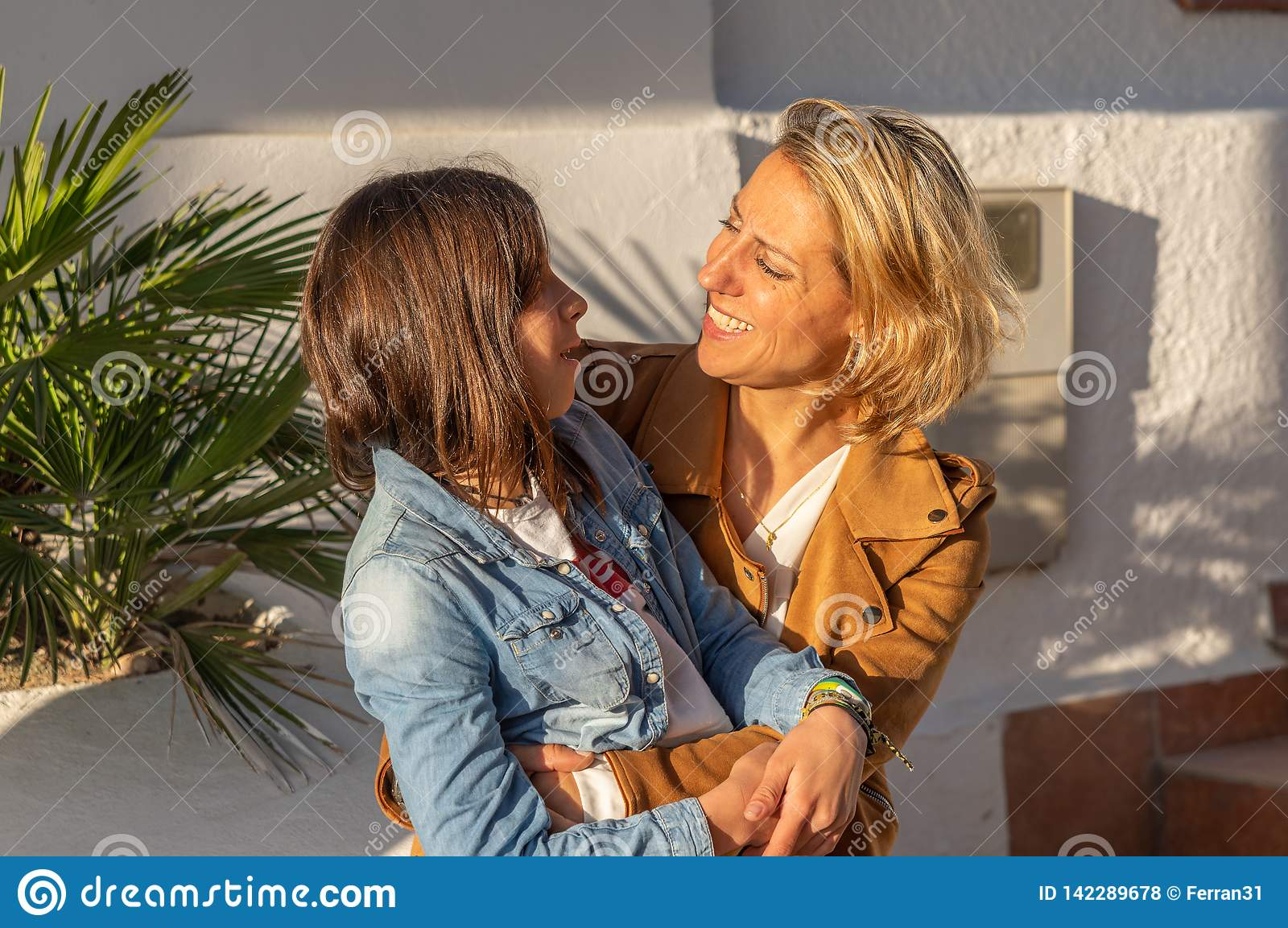 Mother and daughter hugging each other in mediterranean coastal town