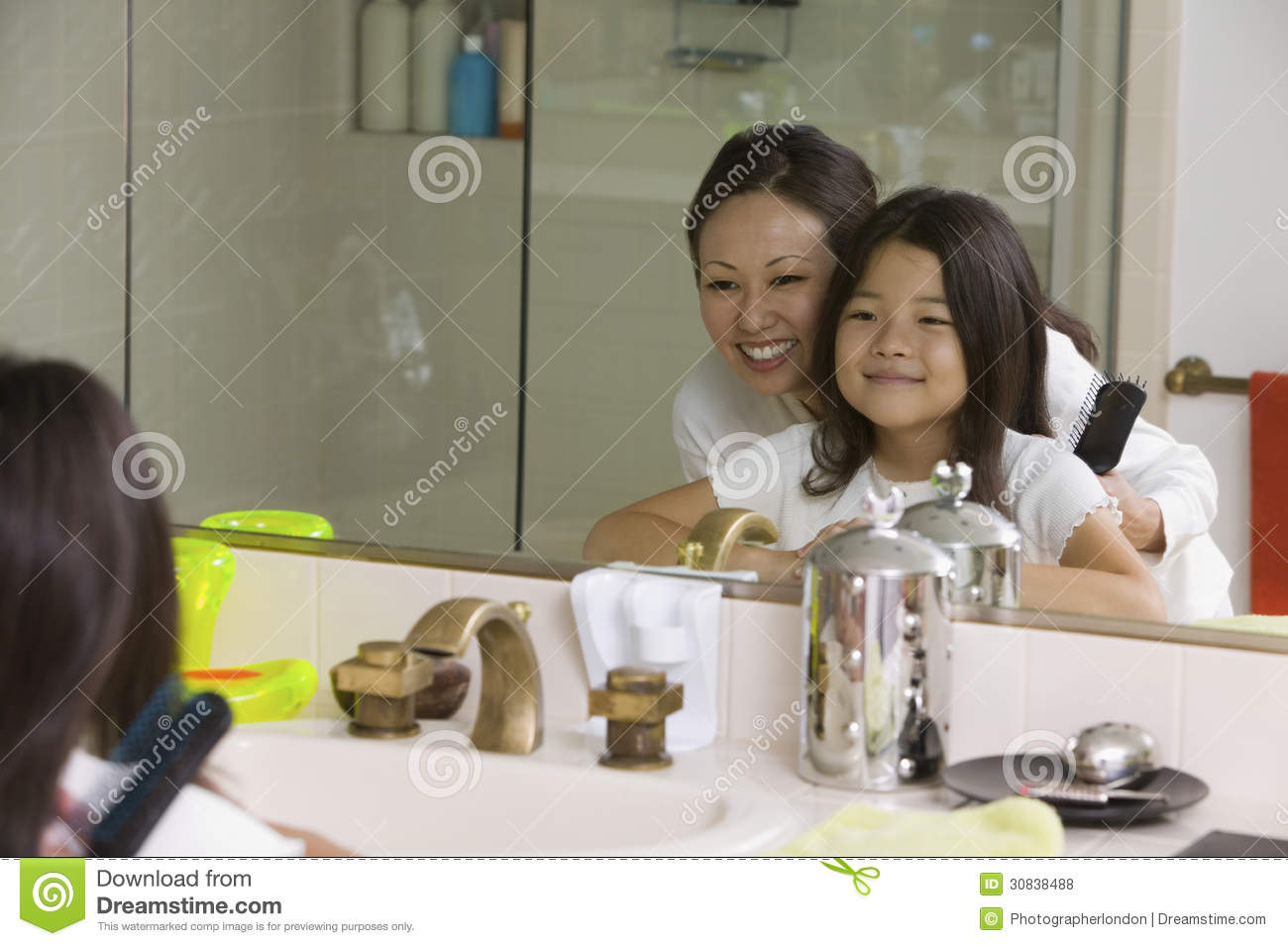 Mother And Daughter Looking At Reflection In Bathroom