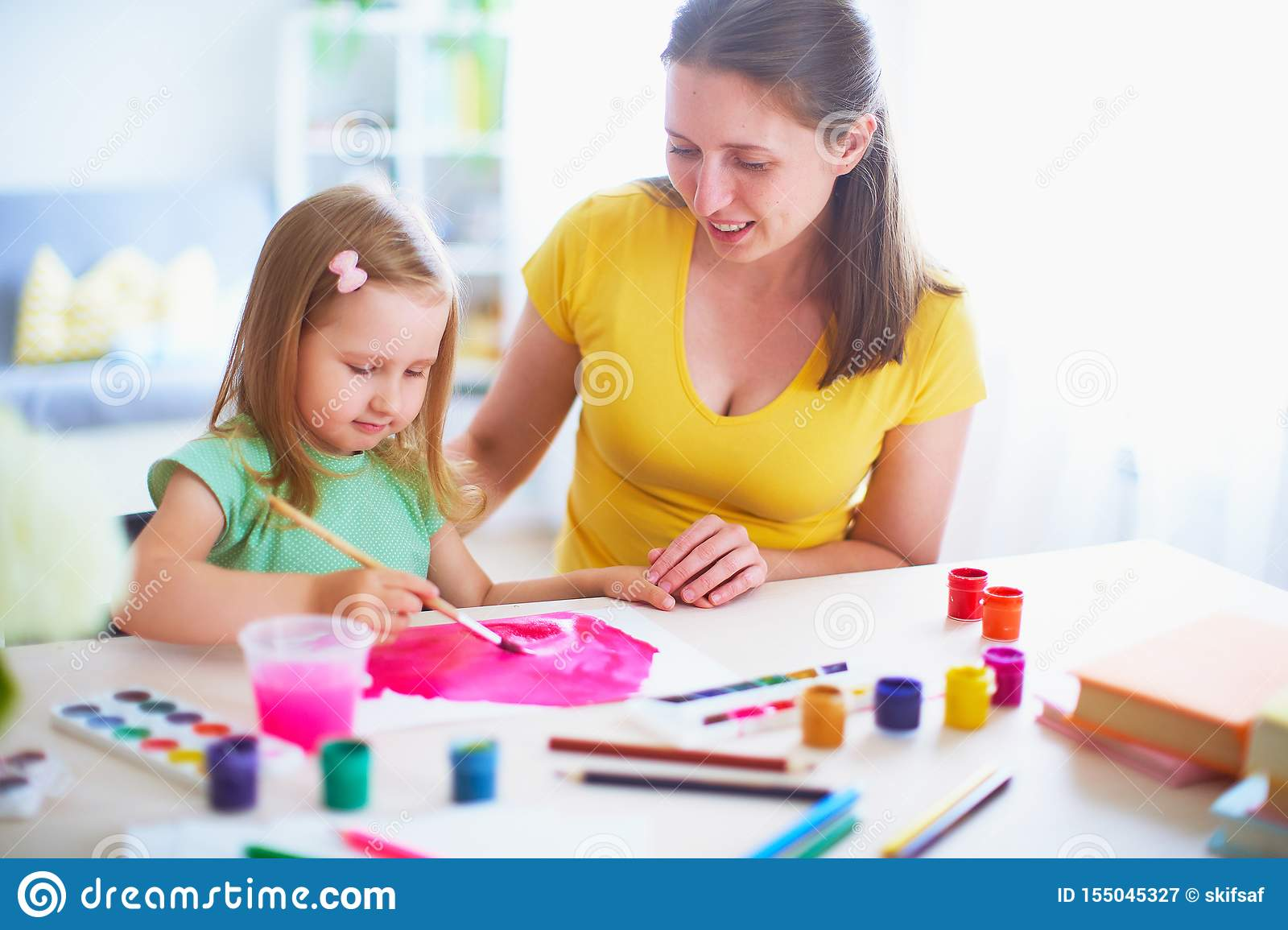 Mother daughter paints watercolor on a sheet of paper sitting at home at the table in a bright room