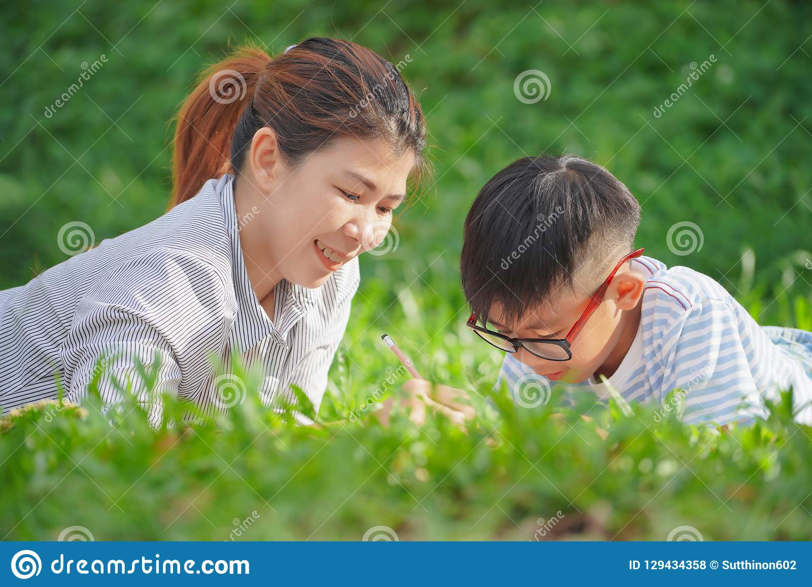 Mother with daughter in the park, Mother teaching son write on notebook and sitting picnic in the park.