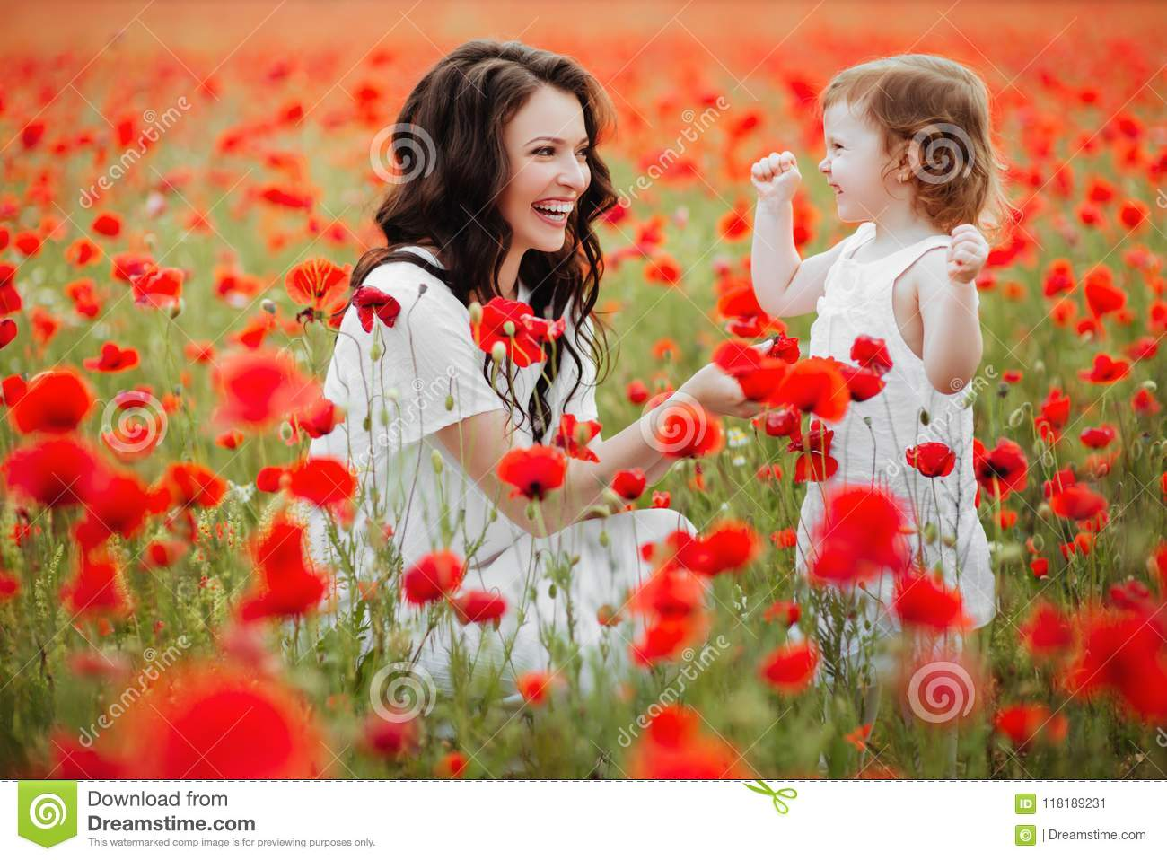 Mother and daughter playing in flower field