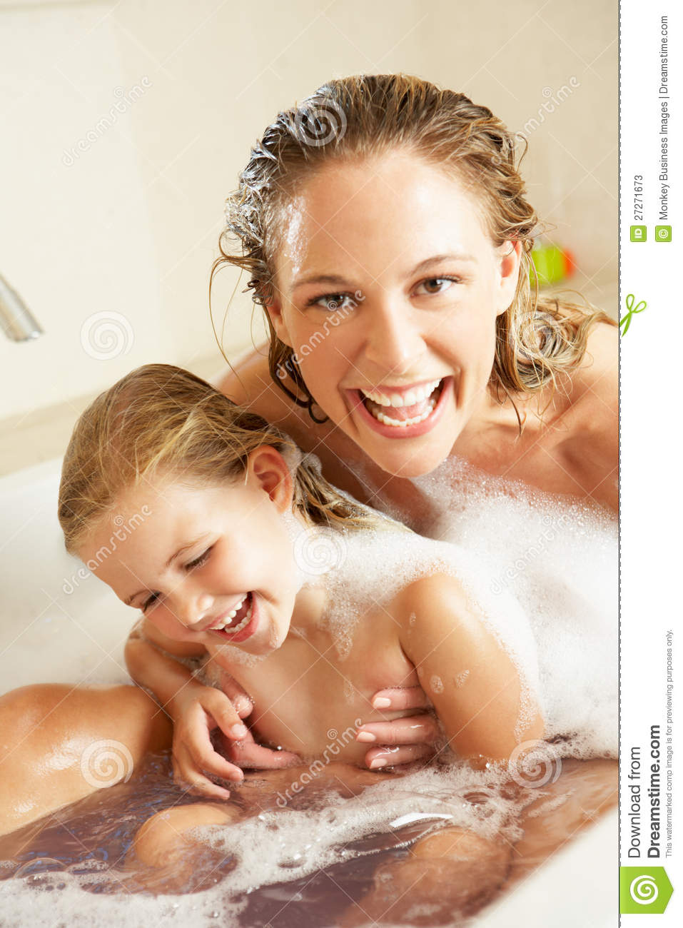 Mother And Daughter Relaxing In Bubble Filled Bath Laughing.