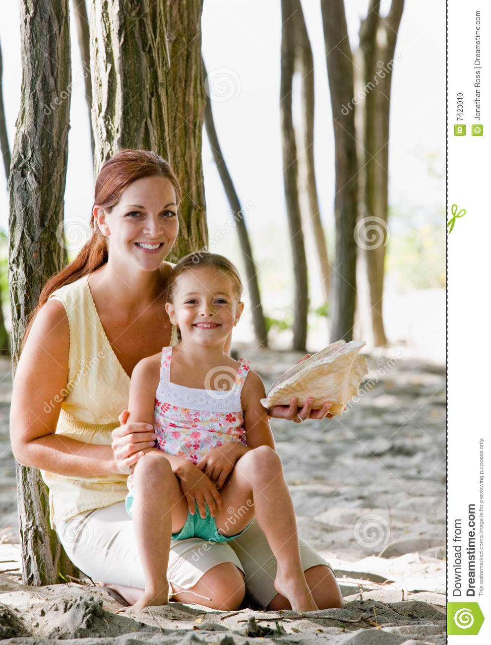 Mother and daughter with seashell