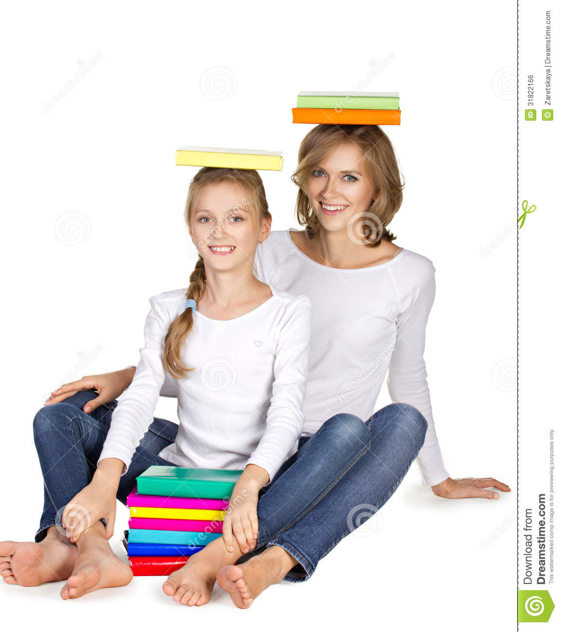 Mother and daughter sitting on the floor with books on heard