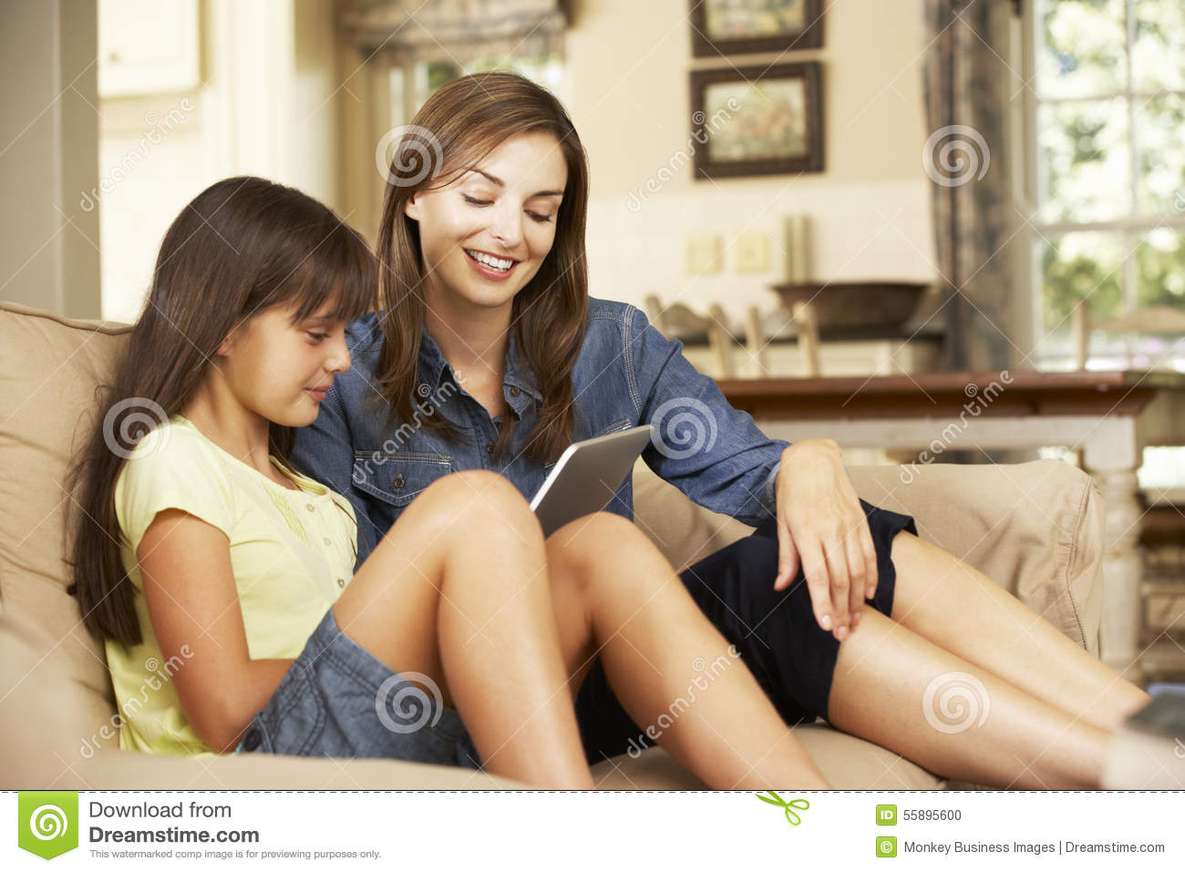 Mother And Daughter Sitting On Sofa At Home Using Tablet Computer