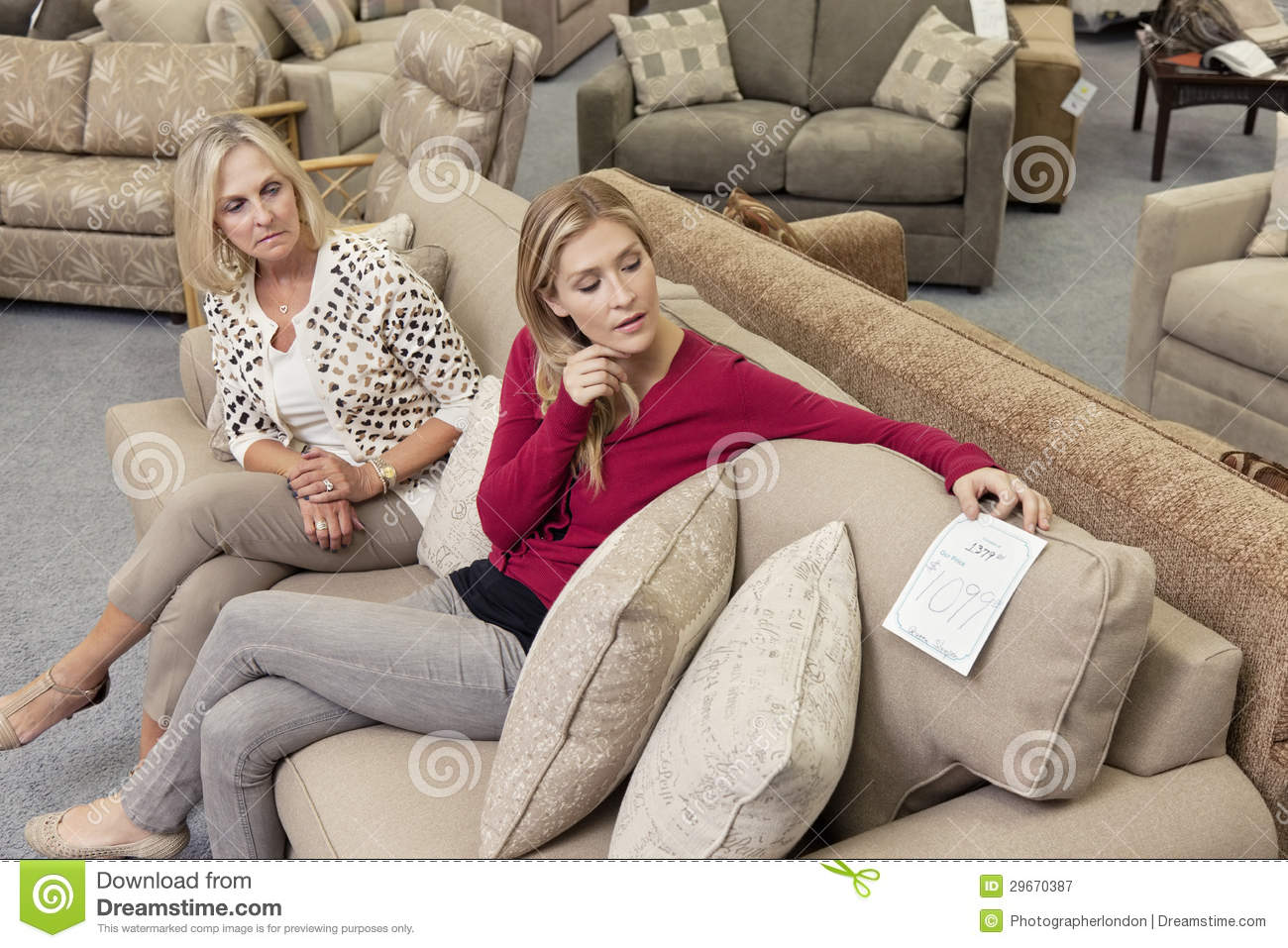 Mother And Daughter Sitting On Sofa While Looking At Price Tag In - Red tag furniture