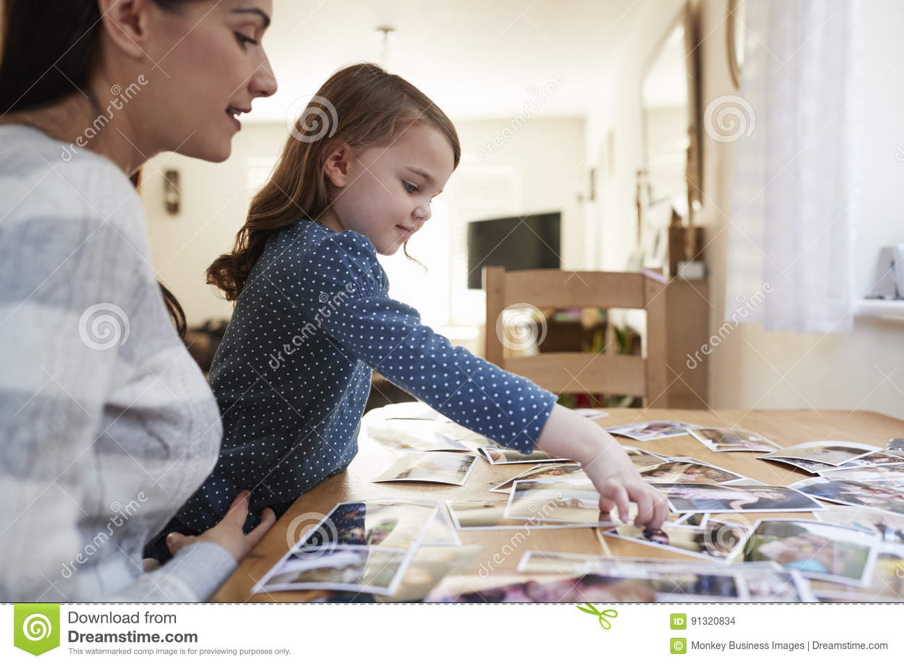 Mother And Daughter Sitting At Table Looking Photos