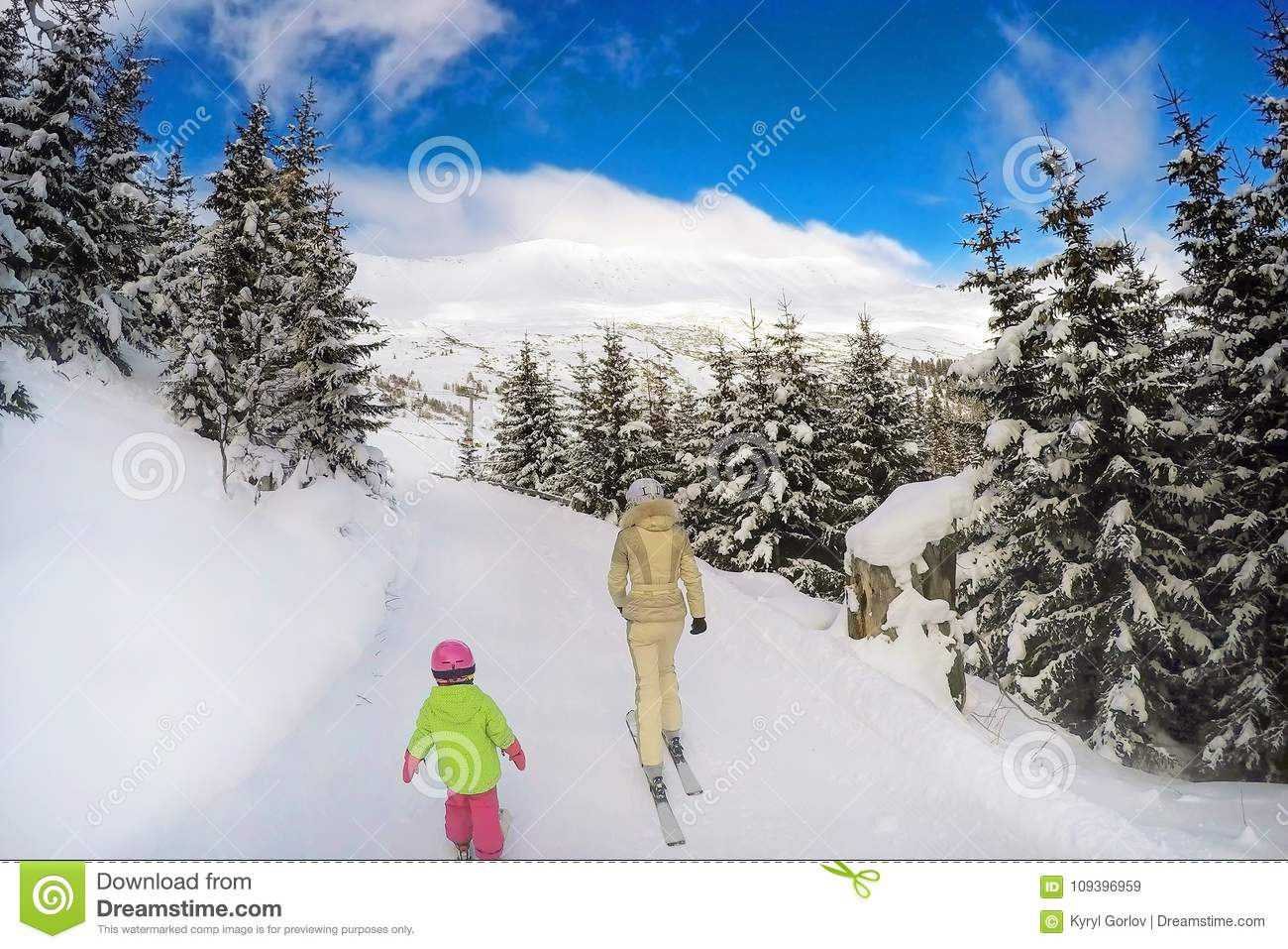 Mother and daughter skiing in forest. Back view. Bright sunny winter day. End of winter vacation concept. Closure of winter sport
