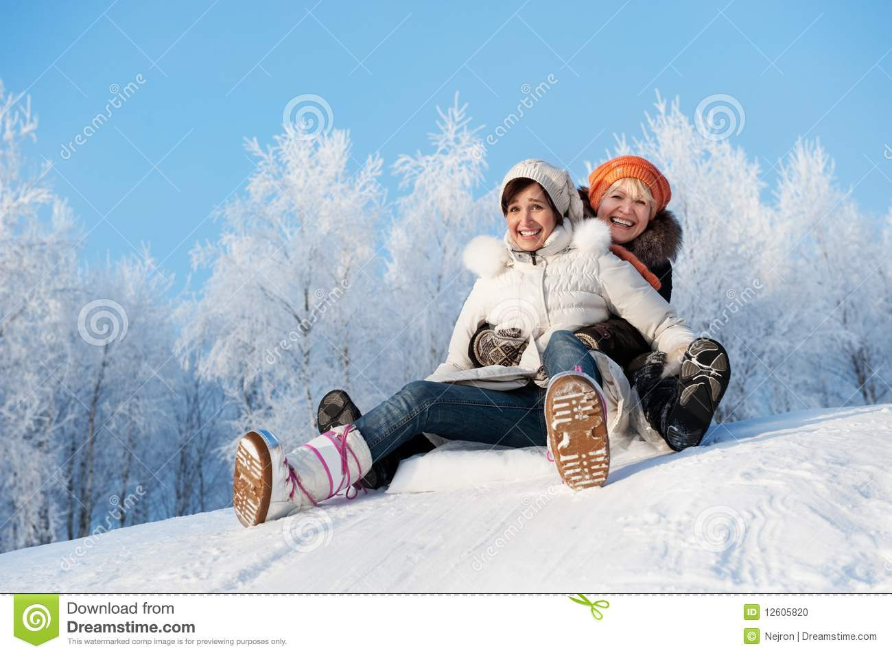 Mother and daughter sliding in the snow