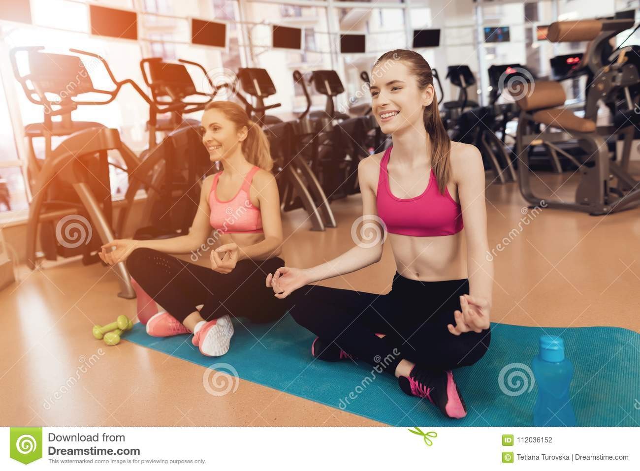Mother And Daughter Doing Yoga Poses At The Gym They Look Happy