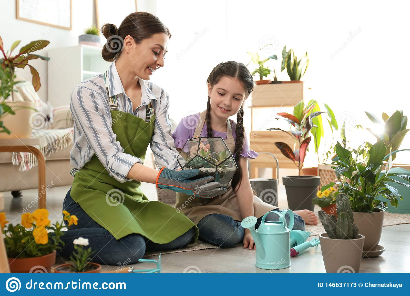 Download Mother And Daughter Taking Care Of Plants On Floor Stock ...