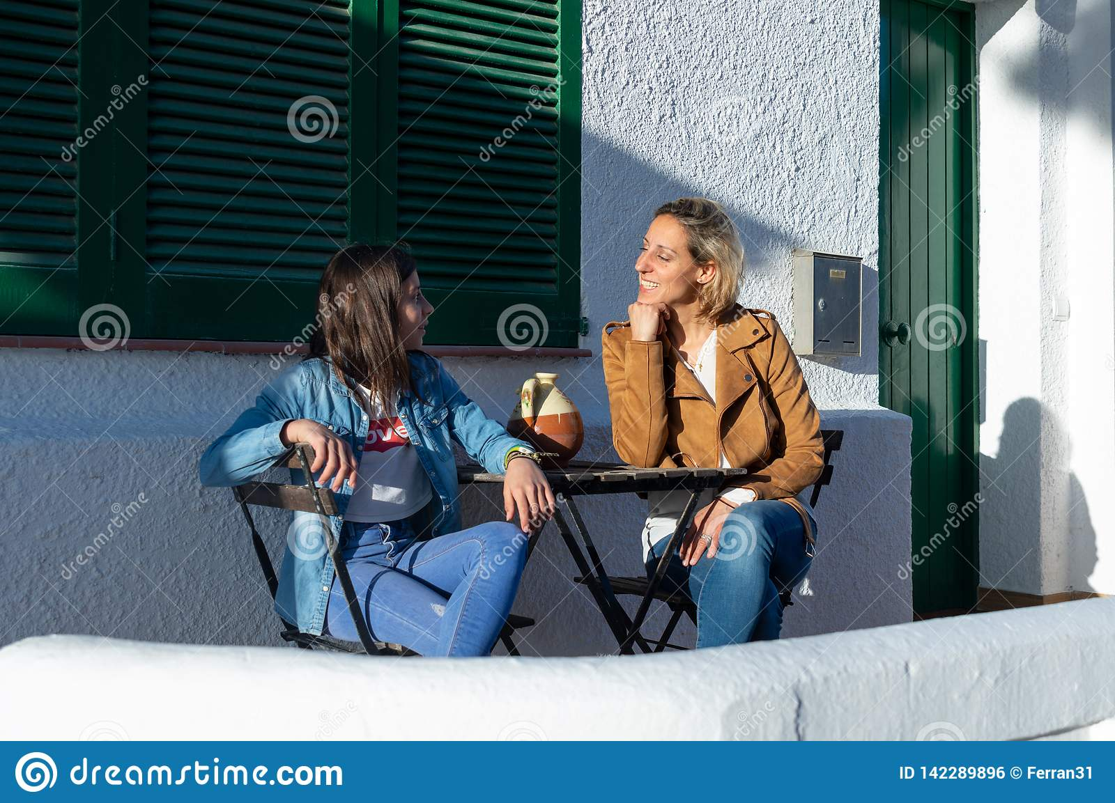 Mother and daughter teenager sitting on green furniture terrace in typical european coastal town of Barcelona, in Spain