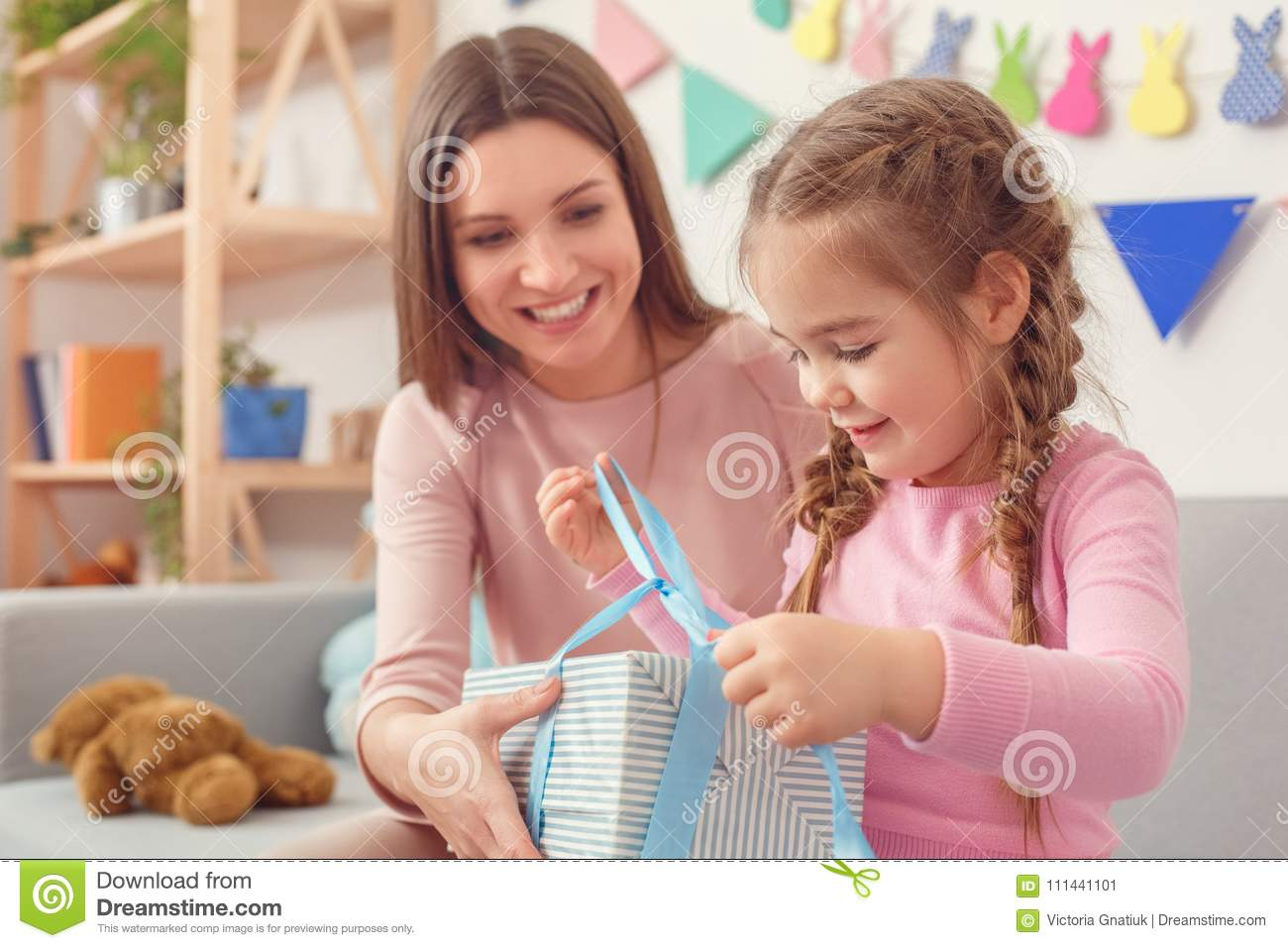 Young Mother And Little Daughter Together At Home Celebration Concept Girl Holding Birthday Present Opening Ribbons Excited