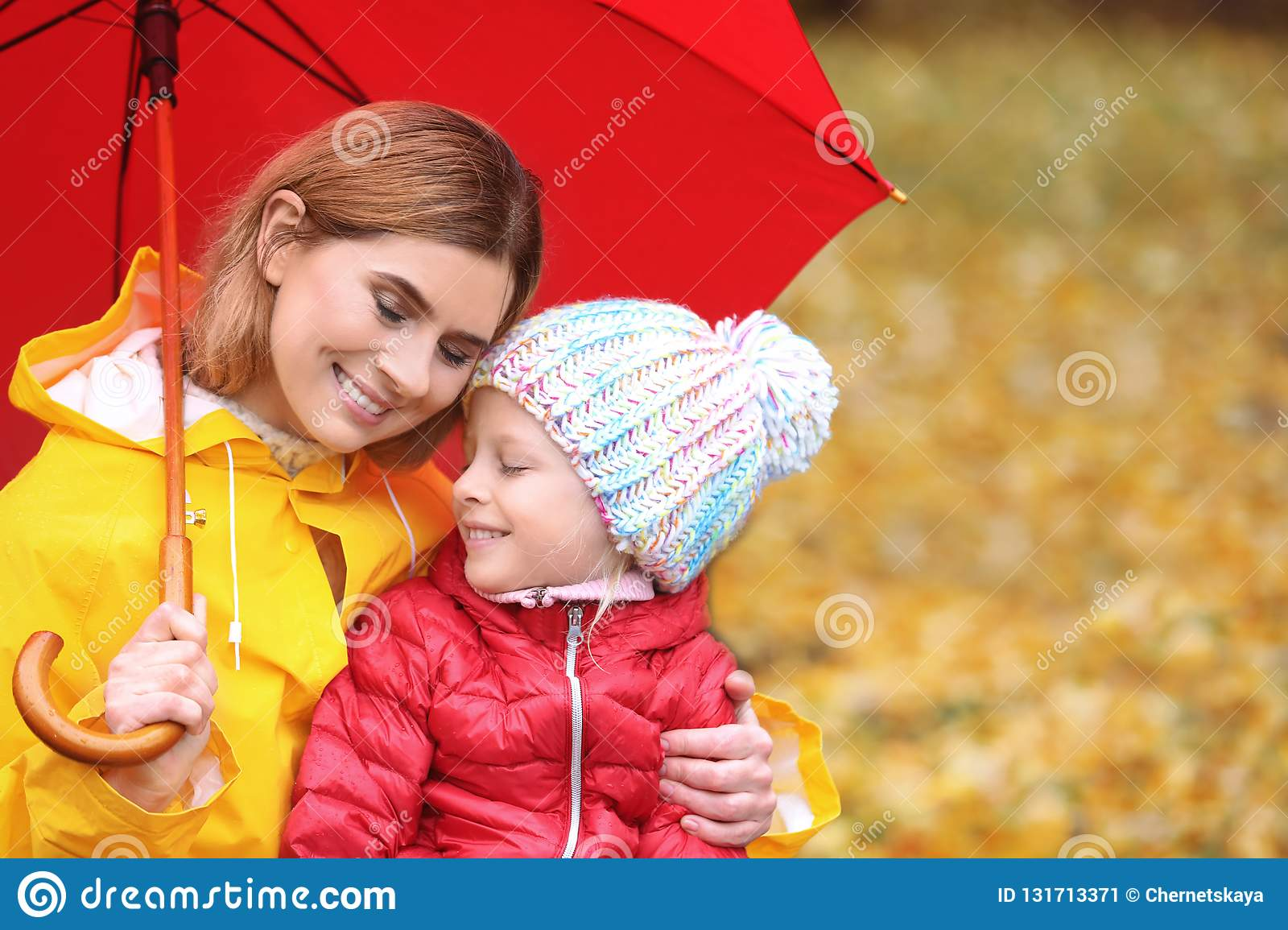 Mother and daughter with umbrella in autumn park