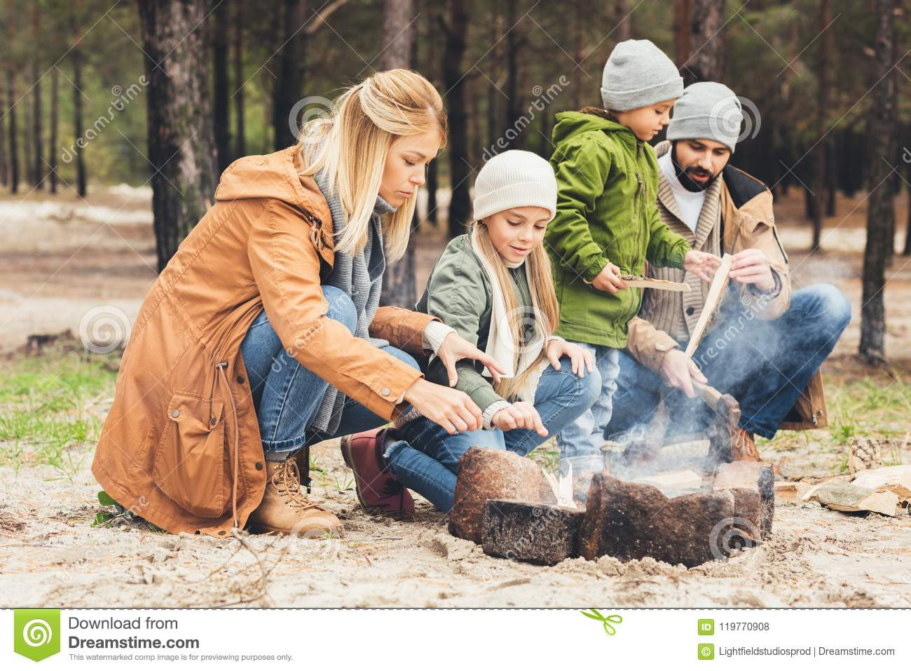 mother and daughter warming hands with bonfire while father and son