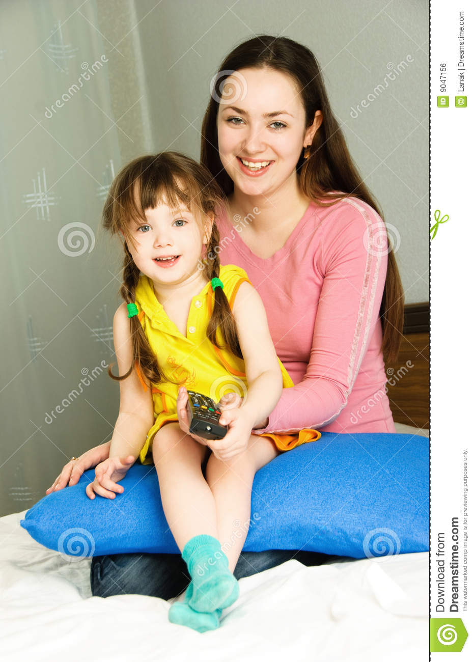 Watch Mom In Bedroom Camera: Mother And Daughter Watching TV Stock Photo