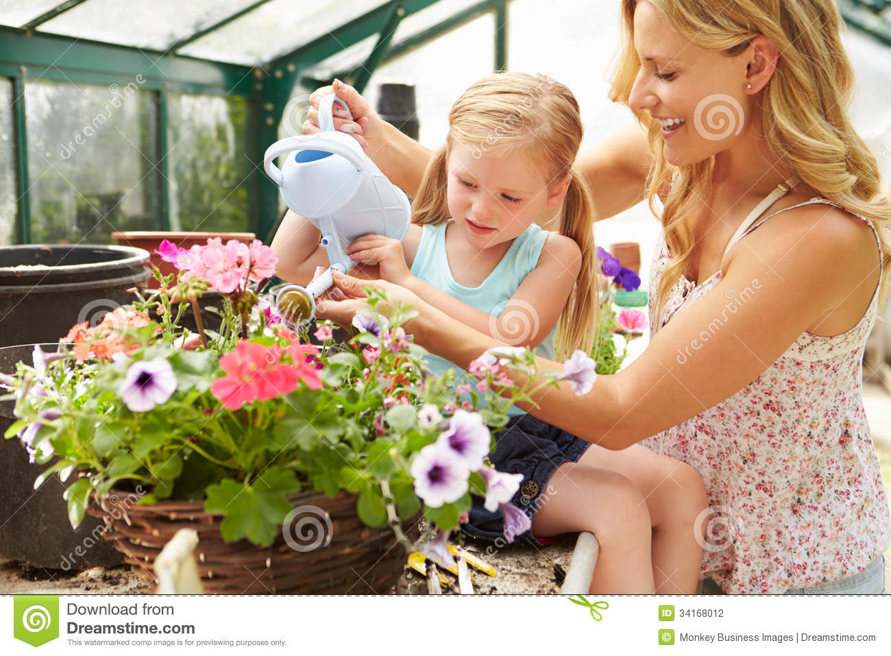 Download Mother And Daughter Watering Plants In Greenhouse Stock ...