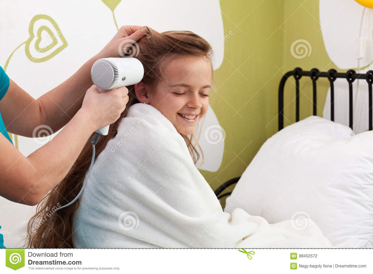 Mother drying her little girl`s hair after bath